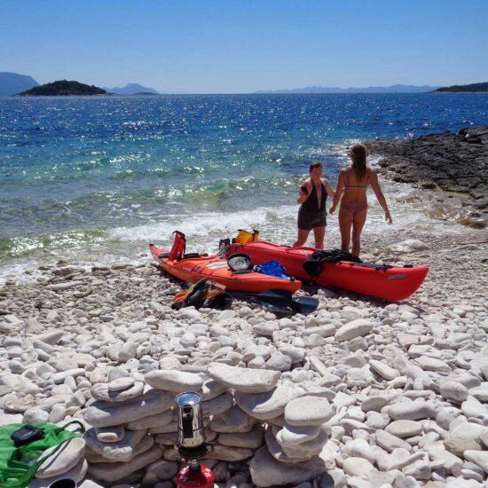 2 girls on the pebblestone beach with kayaks